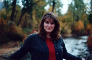 Karalene stands in front of a stream in the forest