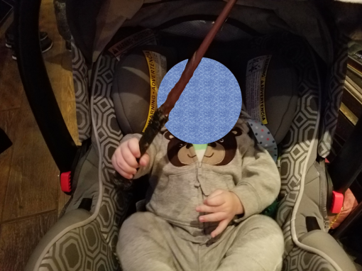A baby in a stroller holding a replica of Harry Potter's magic wand