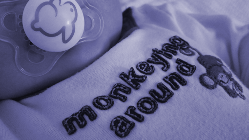 "A close up of baby wearing clothing that says ""monkeying around"""