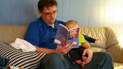 A man reading The Fantasitc Mr. Fox to an infant